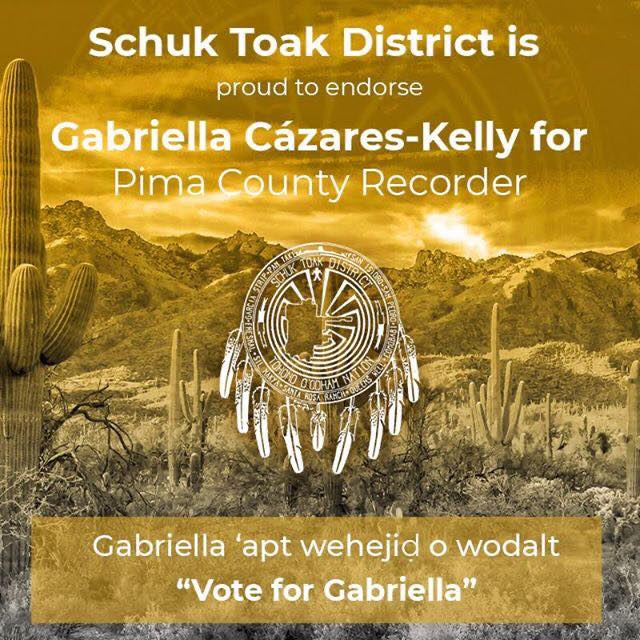 "Image Description A yellow tinted photo of mountainous desert with the following text written in white: Schuk Toak District is proud to endorse Gabriella Cázares-Kelly for Pima County Recorder. Gabriella 'apt wehejid o wodalt! ""Vote for Gabriella!"" A District Logo is in the center of the graphic. It is a Man in the Maze Symbol, with a cut out of the Schuk Toak District Boundaries, The text: Schuk Toak District, Tohono O'odham Nation and the names of the communities of Schuk Toak: San Isidro, San Pedro, Comobabi, Queen's Well, Santa Rosa Ranch, Sil Nakya, Fresnal, Garcia Strip and Pan Tak are incorporated into the seal. Nine feathers hang from the bottom of the seal to represent the 9 communities."
