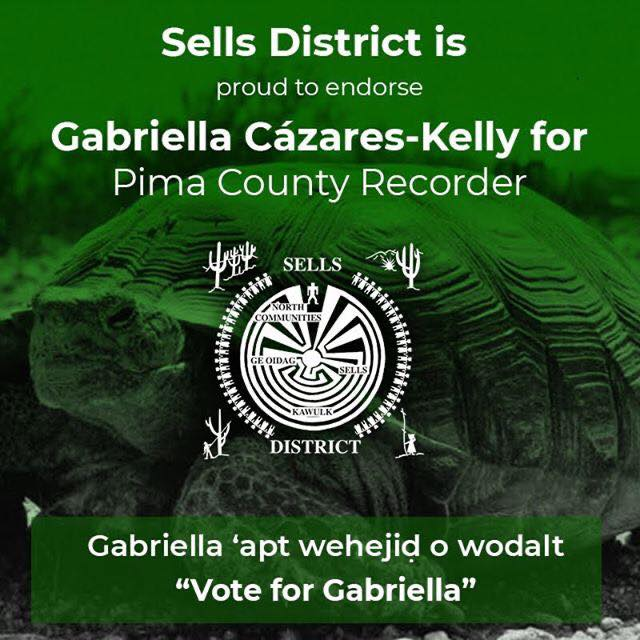 "Image Description: Green graphic with a turtle background and the following text: Sells District is proud to endorse Gabriella Cázares-Kelly for Pima County Recorder Gabriella 'apt wehejid o wodalt. ""Vote for Gabriella"" The Sells District Seal is centered in the document. The seal shows dancers surrounding the Man in the Maze symbol. There are cactus, mountains, and people harvesting bahidaj (saguaro fruit) in each of the 4 corners. The text: North Communities, Ge Oidag, Sells and Kawulk overlay the maze."